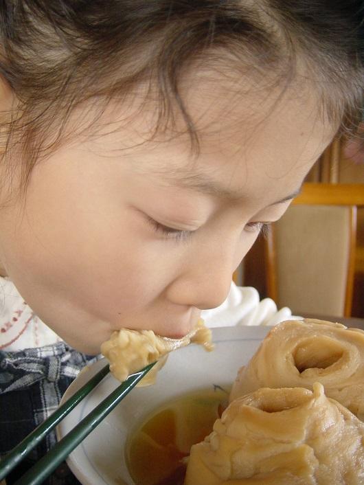 はじ麩の煮物を食べる娘